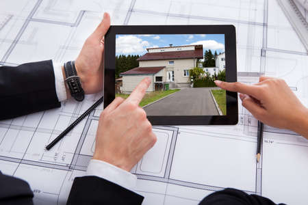 Cropped image of architects with digital tablet looking at photo of the house  Stock Photo