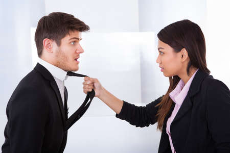 Side view of angry businesswoman holding businessmans tie in office