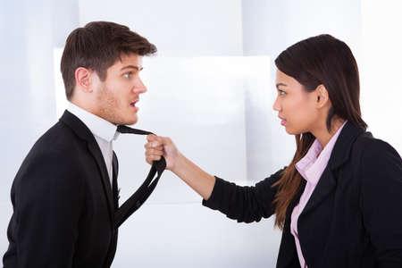 dominacion: Vista lateral del lazo enojado empresaria celebración de negocios en el cargo