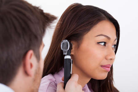 otoscope: Side view of male doctor examining patients ear with otoscope in clinic