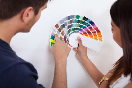 swatches: Young couple choosing color for wall from swatches at new home Stock Photo