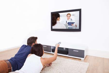 personas viendo television: Joven pareja viendo televisión mientras está acostado en la alfombra en su casa