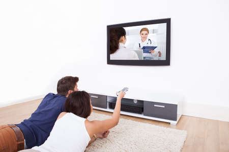 sofa television: Young couple watching TV while lying on rug at home Stock Photo