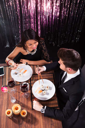 High angle view of loving young couple having meal at restaurant table photo