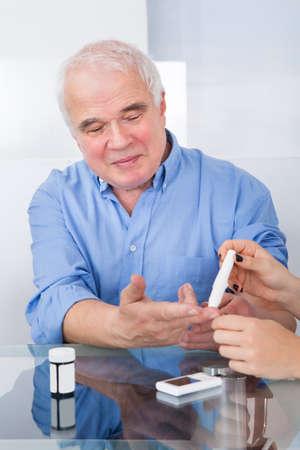 Vrouwelijke arts met behulp van lancetvisje op senior man aan het bureau in kliniek