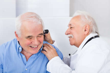 otoscope: Smiling male doctor examining senior mans ear with otoscope in clinic