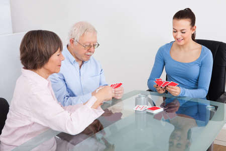 Young female caretaker playing cards with senior couple at table in nursing home photo