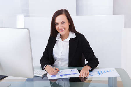 Smiling young businesswoman using computer at desk in office photo
