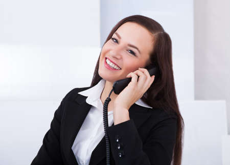 noting: Portrait of happy young businesswoman using telephone at desk in office