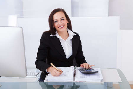 Portrait of happy businesswoman calculating tax at desk in office