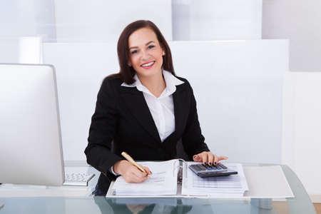 calculadora: Retrato de mujer de negocios feliz calcular el impuesto en el escritorio en la oficina
