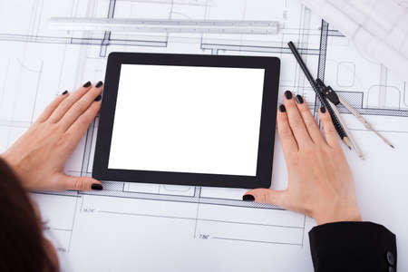 High angle view of architect woman with digital tablet and blueprint at desk in office photo
