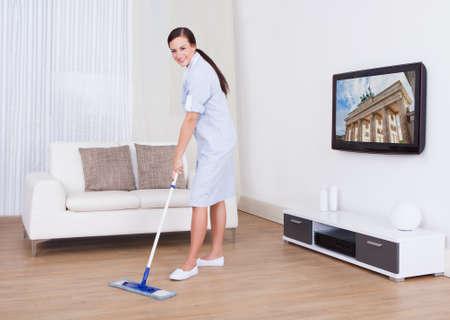 servicio domestico: Retrato de cuerpo completo de la joven planta de limpieza de limpieza con la fregona en su casa Foto de archivo