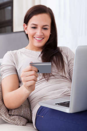 Smiling young woman using credit card and laptop to shop online at home photo