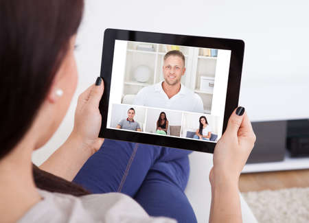 webcam: Cropped image of young woman using tablet for video conference at home Stock Photo