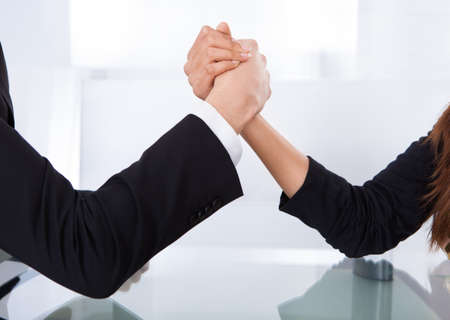 Close-up view of business colleagues arm wrestling at desk in office photo