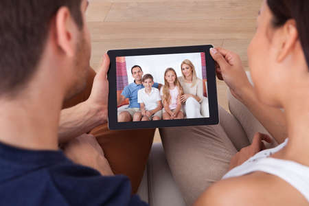 house call: High angle view of young couple using digital tablet together at home