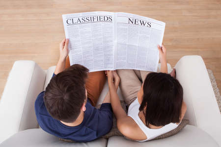 High angle view of young couple reading newspaper together on sofa at home photo