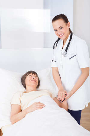 Portrait of happy female doctor consoling senior woman lying in bed at clinic photo