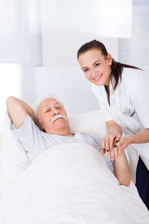 Portrait of happy female doctor consoling senior man lying in bed at clinic photo