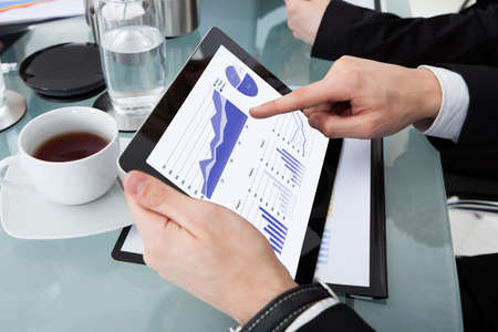Cropped image of businessman using digital tablet with colleagues at desk in office photo
