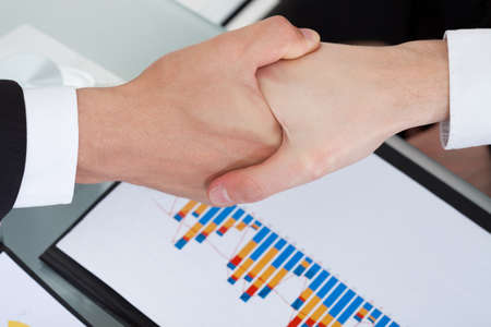 Cropped image of business colleagues shaking hands in office photo