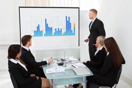 Businessman giving presentation on projector screen to colleagues in office