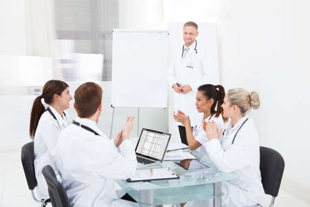 Team of young doctors clapping for colleague after presentation at desk in clinic photo