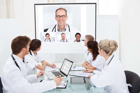 projection screen: Team of doctors looking at projector screen in video conference meeting at hospital