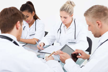 Team of doctors working at desk in clinic photo