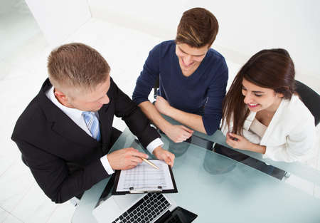 financial adviser: High angle view of financial advisor explaining investment plan to couple at office desk