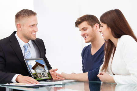 Businessman showing photo of a new home to couple on laptop at office desk photo