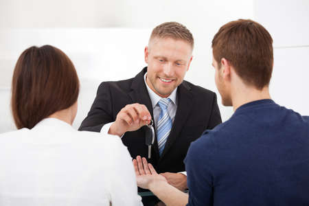 Happy agent giving car key to couple in office