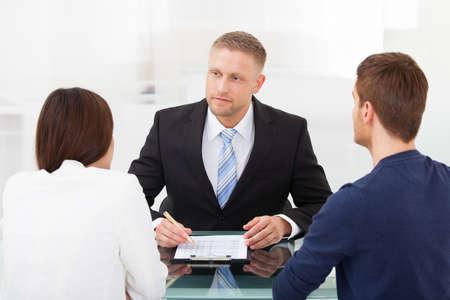 若いカップルのオフィスの机で金融アドバイザーのコンサルティングの背面図 写真素材
