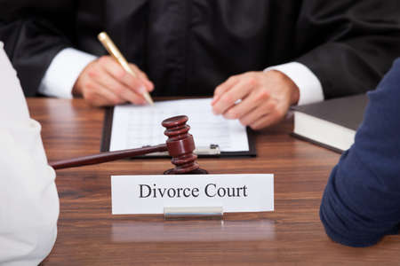 cropped image: Cropped image of couple with judge writing at desk in court Stock Photo