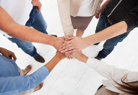 Cropped image of businesspeople stacking hands in office photo