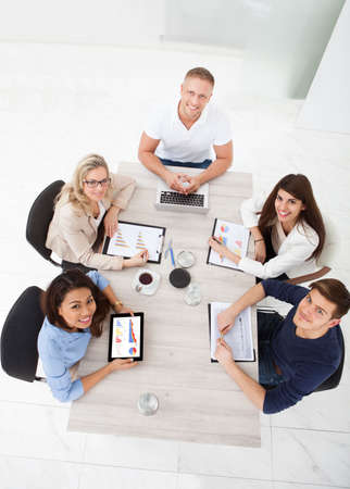 five people: High angle view of business team working at office desk in meeting