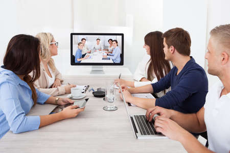 Business team attending video conference at desk in office photo