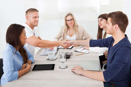Businessmen shaking hands in meeting at office desk photo