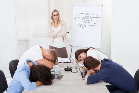Rozzlobený podnikatelka při pohledu na unavené kolegy na spaní při prezentaci v kanceláři
