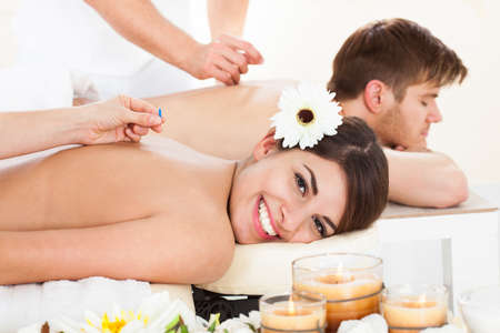Portrait of happy woman undergoing acupuncture at beauty spa photo
