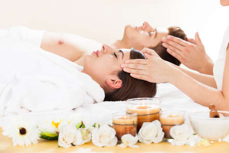 Young couple receiving head massage at beauty spa photo