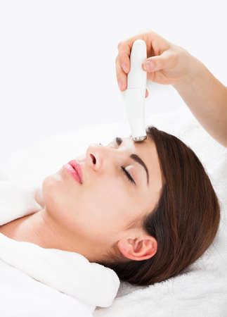 Beautiful young woman receiving microdermabrasion therapy at beauty spa photo