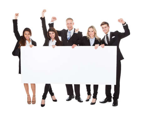 Full length portrait of confident businesspeople holding blank banner against white background photo