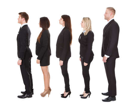 side profile: Full length side view of welldressed businesspeople standing in a line over white background Stock Photo