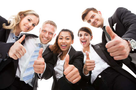 Low angle portrait of business people gesturing thumbs up against white background photo