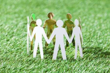 Team of paper people standing in circle on grassy field photo