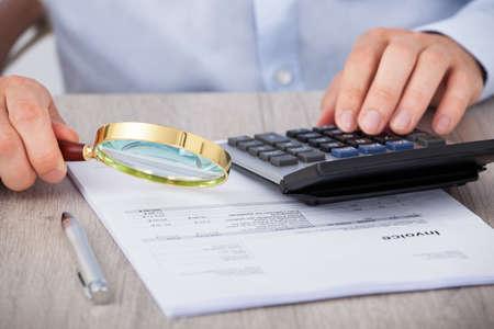 Buik van mannelijke accountant loep financiële documenten op het bureau Stockfoto - 27954224