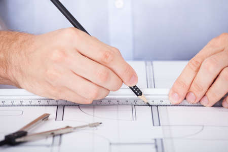 architect office: Cropped image of male architect working on blueprint at desk in office