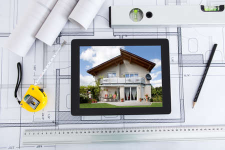 House displayed on digital tablet screen with architects tools over blueprint photo
